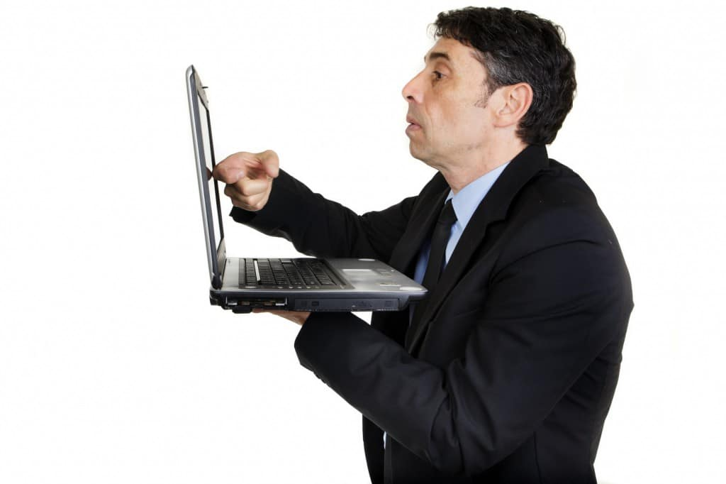 Side view of a serious businessman tapping his laptop screen with his finger as he stands holding it in his hand, upper body portrait isolated on white